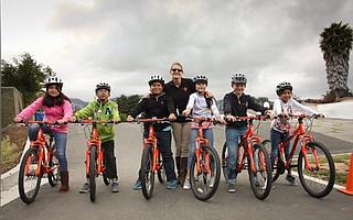 Adams schoolkids and PE teacher Julie Churchman with a new fleet of bikes.