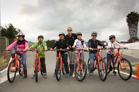 Adams schoolkids and PE teacher Julie Churchman with a new fleet of bikes.