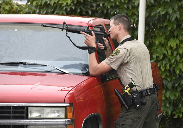 A Sheriff's deputy takes aim during the Motel 6 standoff