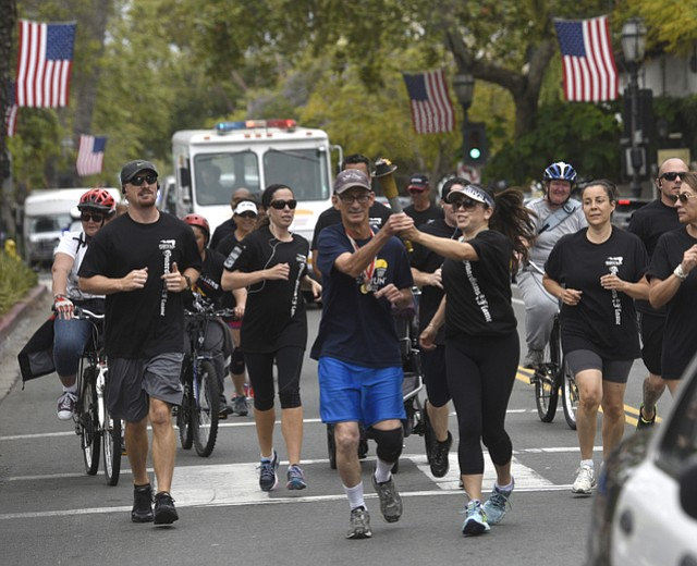 Special Olympics athlete Steve Glick is handed the torch on a run through the streets of Santa Barbara.