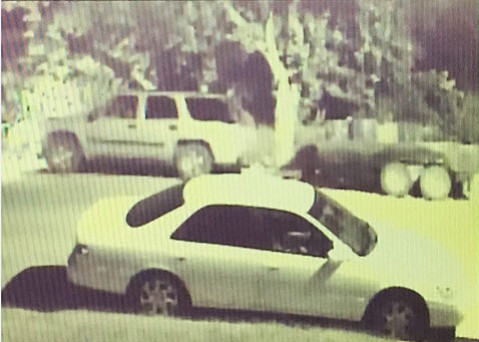 Authorities are asking for the public's help to identify the driver of the SUV in the background of this photo