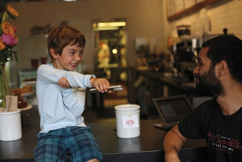 <b>COLD TRUTHS:</b> Four-year-old Nikita Gruzdev interrogated McConnell's Ice Cream scooper Luis Bermudez about the logistics of working behind the frozen bar.