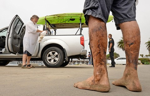 Fisherman Henry Duncan, left, and Bob Seiler stand in the Goleta Beach parking lot after encountering a large oil sheen off the pier. County Fire Chief Eric Peterson in the background surveys the scene.