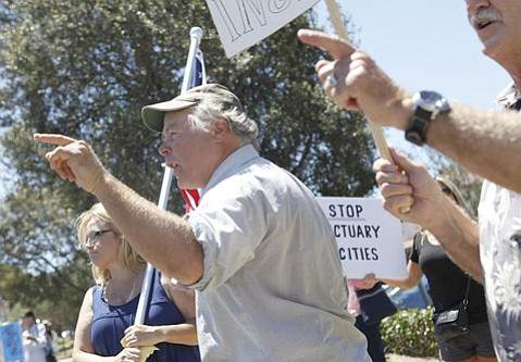"Steve Redgate shouts, ""Protect our women,"" at a group opposite. The two groups gathered near the Santa Maria courthouse — one to protest the rape and death of a 64-year-old woman allegedly at the hands of an illegal immigrant, the other to protest the use of a tragedy to further a political agenda."