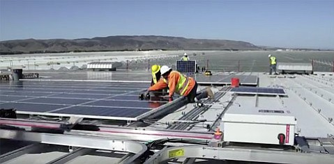 Workers install the 4,032-panel solar array developed by REC Solar that will power Windset Farms. (REC Solar Company)
