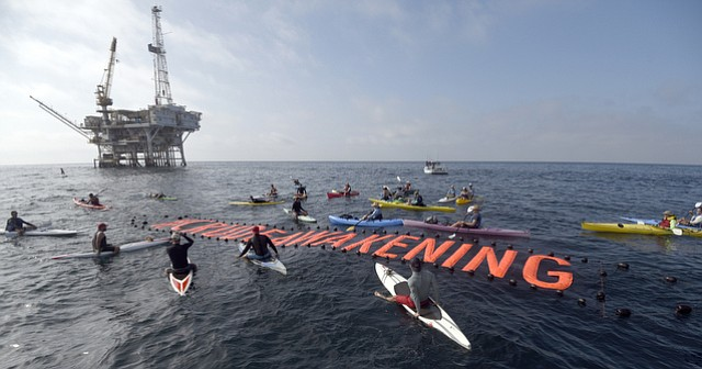 Kayakers, surfers, and boaters head out to Platform Holly in the Santa Barbara Channel to protest oil drilling and unfurl a #crudeawakening banner. (Aug. 22, 2015)