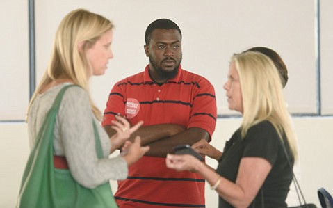 <b>HOT TOPIC: </b> Laura Burton Capps (left), now consulting for Airbnb, and Toussaint Miles (center) talk at a city workshop.