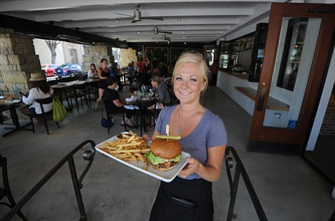 Allison Kearney presents a Benchmark burger in the summer of 2014, soon after the Bennett family opened the restaurant.