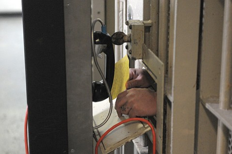 <strong>OTHER END OF THE LINE:</strong> An inmate makes a call from jail.