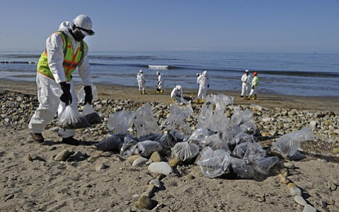 <strong>PAYING THE PIPER:</strong> Cleanup workers bag oily sand right after the spill.