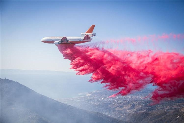 An air tanker drops retardant along the Cold Springs Canyon side of the ridge to provide a dampening effect on the fire.