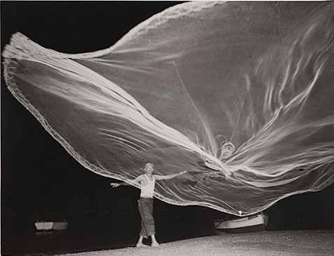 "<b>EVERYDAY OBJECTS:</b>  Photographer Raul Corrales's ""Fishing Nets/La atarraya"" (circa 1950) captures a lone fisherman from the village of Cojimar, Cuba, flinging a white net, its light fabric floating improbably far into the air. This is just one of the 47 works created since the 1930s by artists living and working in Latin American countries being shown in the SBMA exhibit <i>Looking In, Looking Out.</i>"