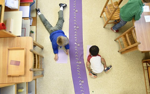 Alton Carmean (left) and Brandon Kim are focused on the task at hand at the Montessori Center School.