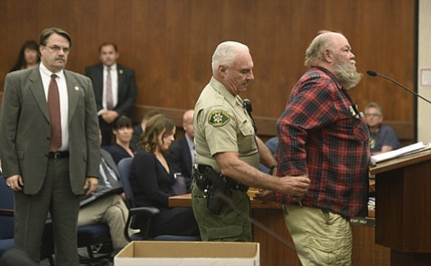 "Sheriff deputies put the cuffs on homeless advocate Bob ""Protest"" Hansen."