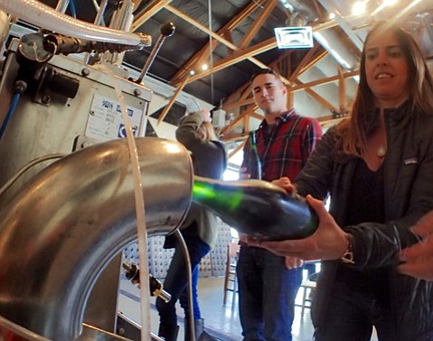 <strong>BUBBLE FEST:</strong> Gabi Larkins of Villa and Vino Divino disgorges a bottle of Potek bubbly as Wine Cask's Branden Bidwell watches.