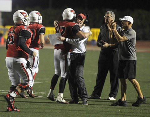 <strong>COMPETITIVE CONCERNS:</strong> Bishop Diego coach Tom Crawford hugs Matt Shotwell (42) after winning their first CIF play-off game against Newbury Park in November 2014.