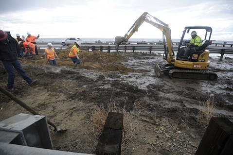Caltrans employees work to open clogged median drainage culverts that caused freeway flooding Tuesday morning.  (Jan. 5, 2016)