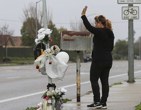<strong>LOST: </strong> Blanca Rodriguez, of Santa Maria, prays at a memorial for Marcos Ramos, 15, killed last month.