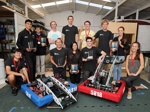 <strong>BARN BUILD:</strong>  Kally Zheng (center) and Riviera Robotics with Team 5818 practice (blue) and competition robots.