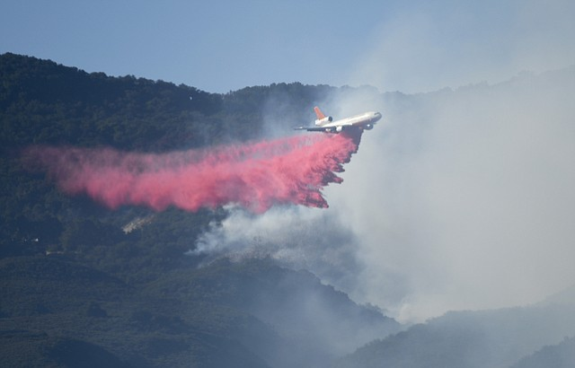 A DC-10 drops a load of Phos-chek on the Scherpa Fire. (June 15, 2016)
