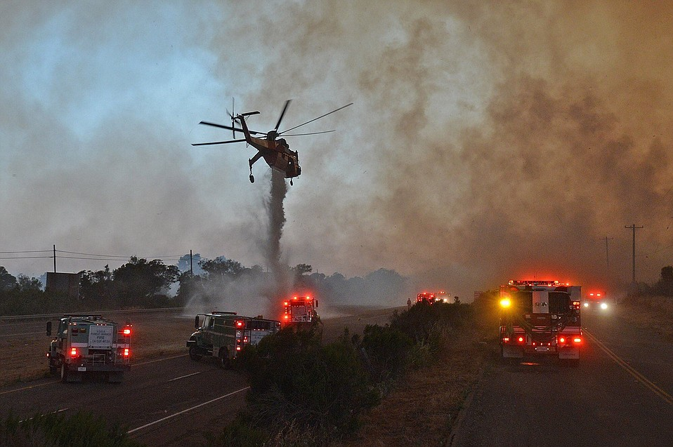A skycrane helicopter makes a drop on the Highway 101 center divider at El Capitan State Park