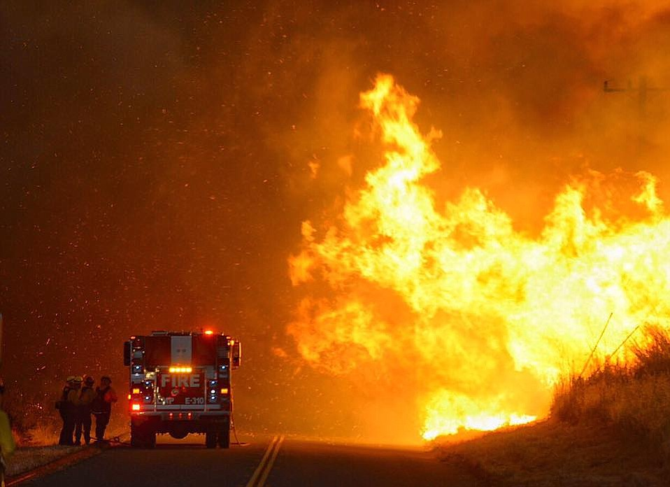 Firefighters take shelter behind their engine as flames advance near El Capitan State Park.
