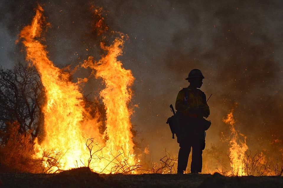 A firefighter keeps a watchful eye Friday night on flames on a ridgeline near El Capitan Ranch