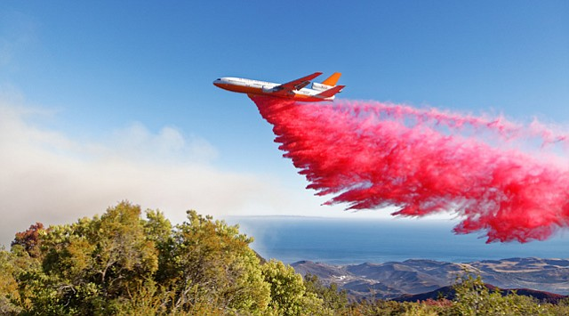 <b>BIG GUNS: </b> The venerable DC-10 (above) lays down a containment line of fire retardant high along the steep, chaparral-choked canyons near West Camino Cielo.