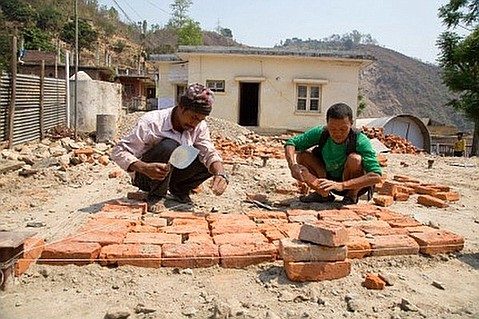 Workers lay brick foundation for the Mahadevesi Birthing Center, destroyed in last April's devastating 7.8-magnitude earthquake.
