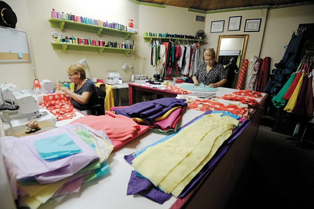 """A SAGA OF SEWING:  Seamstress Maria Lazcano (pictured right) often worked late into the night with her sister Socorro Avila to make more than 90 dresses for this year's Fiesta. """"It's very emotional for me to see the dancers up onstage in a costume I've made for them,"""" said Lazcano. """"It's very satisfying."""""""