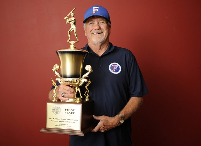 Coach Bill Pintard just back in town from a 24 hour bus ride from Wichita, holds the Foresters' 6th Championship trophy.