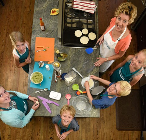 <b>STUDENT CHEFS:</b> Nancy Martz teaches kids to cook in her Apples to Zucchini class, shown here making fresh corn tortillas and guacamole.