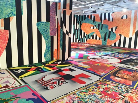 <b>EXPLOSIONS IN SPACE:</b> In its MCA exhibit, the art collective assume vivid astro focus uses custom wallpaper, video projection, and dozens of brightly colored area rugs to transform the space into a dizzying, challenging, frequently satisfying postmodern rec room.