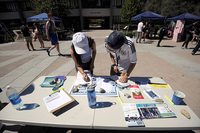 <b>COUNT ME IN:</b> First-year UCSB student Woodrow Davidson (right) helps Vanessa Alvarez register to vote.