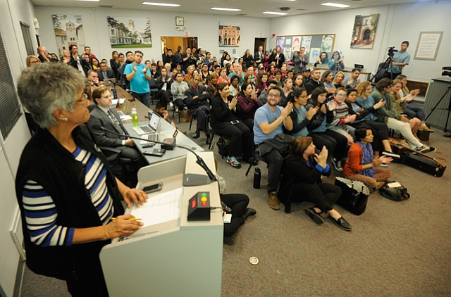 <b>BIG TURNOUT:</b> Overflowing into a backroom and out the side doors, the crowd at Tuesday night's school board meeting applauded district communications coordinator Barbara Keyani (left, standing) as she read a resolution declaring Santa Barbara schools as safe zones against all stripes of prejudice.