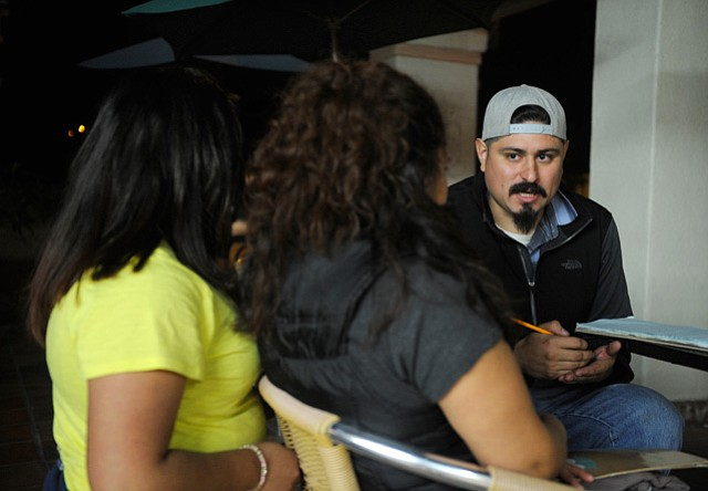 <b>UPSIDE DOWN: </b> Organizer Frank Rodriguez (right) counsels two tenants recently evicted from 520 West Carrillo Street. Part of a family of four, these five-year tenants were given notice in October, moved out by December 1, and still don't know if they'll get their security deposit back.