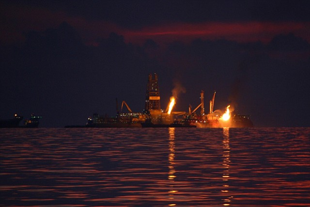 Flames from burning natural gas and oil continued months after the <em>Deepwater Horizon</em> oil platform sank in April 2010.