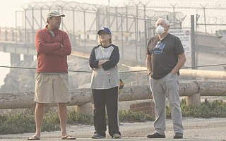 """Mussel Shoals residents (from left) Dan Reddick and Ginny and Joe Crotty """"watch with fingers crossed"""" as the Thomas Fire burns in the foothills across the freeway on December 6, 2017."""