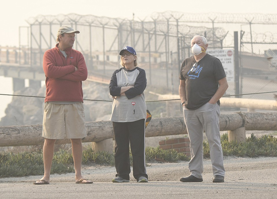 "Mussel Shoals residents (from left) Dan Reddick and Ginny and Joe Crotty ""watch with fingers crossed"" as the Thomas Fire burns in the foothills across the freeway on December 6, 2017."