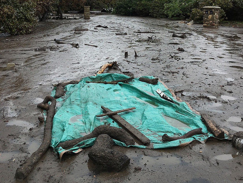 Neighbors placed a green tarp and cross over the remains of a woman killed by the flash floods.