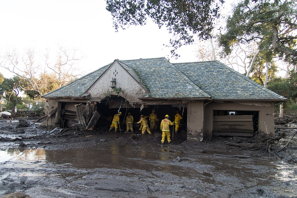 A fire crew enters a home that suffered substantial damage when Montecito Creek veered to the west before crossing over East Mountain Drive, cutting a new path near Sycamore Canyon Road.