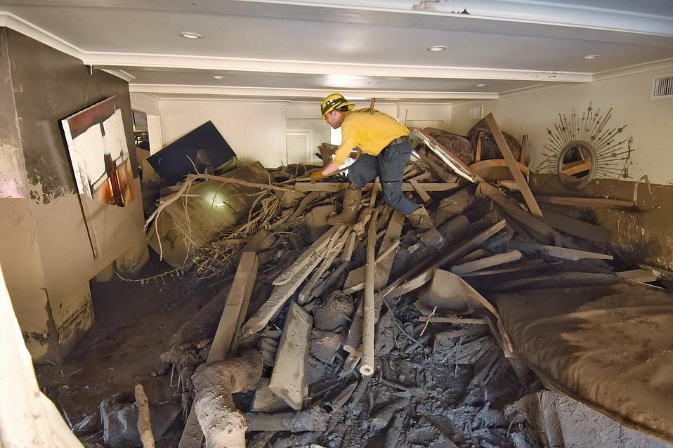 Santa Barbara County firefighter Vince Agapito searches through a destroyed Montecito home