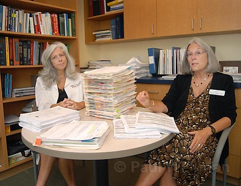 """Paperwork nightmare:  Dr. Cheryl Ellis (left) and Melinda Staveley of the Rehab Institute show paperwork required by """"bounty hunter"""" auditors"""