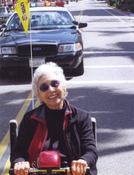 Rita Solinas gleefully brings up the rear in her mobile wheelchair during a State Street march protesting the Iraq War