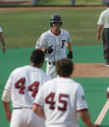 Happy teammates await Kyle Russell as he finishes his grand-slam trot during the Foresters' 11-run second inning.