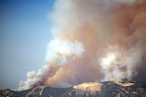 Note use of back firing techniques used here on Alexander Saddle. Firefighters have initiated a burn on the back side of the saddle to develop a primary column that will be used to draw fire set on the front edge of the ridge towards it. As the new fire is set and begins to build its own column (flames and smoke to the left), because the main plume is large enough in size it gradually sucks the column on the left towards it.