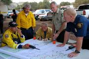 County Fire Deputy Chief Tom Franklin (standing left), area firefighting legend and Los Padres Hot Shot Supervisor Mark Linane (center), and Air Attack Coordinator Brad Joost (standing right) develop a  plan of attack during the early days of the fire.