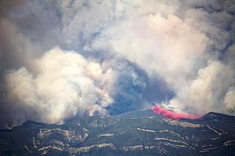 DC-10 lays down a long line of retardant to help fire fighters hold the back fire.