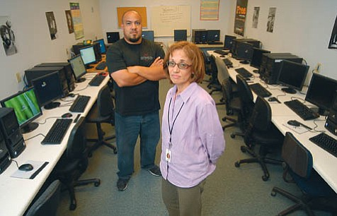 El Puente Community School principal Cecilia Molina and teacher Daniel Umana stand in the school's computer lab. They deny claims that El Puente is toxic.