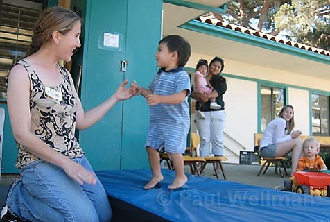 SPARC students bring their children to this daycare center before class. Associate teacher Amy (left) plays with 19-month-old Julian (center).
